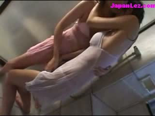 2 jenter i våt clothes kyssing patting henhold den dusj