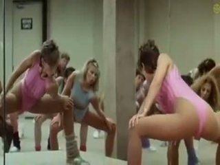 Seksi kanak-kanak perempuan doing aerobics exercises dalam yang keriting cara