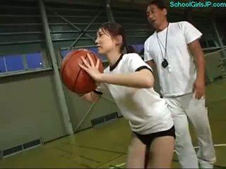 Skolejente i trening kjole fingered av den trener på den basketball trening